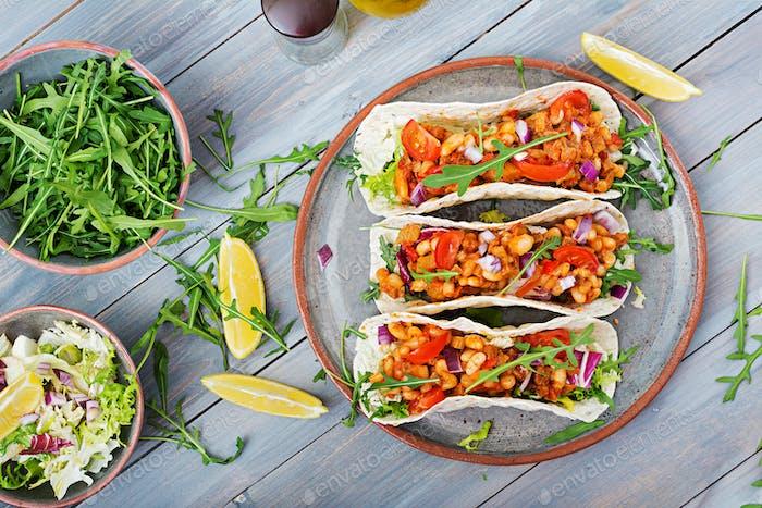 Mexikanische Tacos mit Rindfleisch, Bohnen in Tomatensauce und Salsa. Flache Lag. Draufsicht.