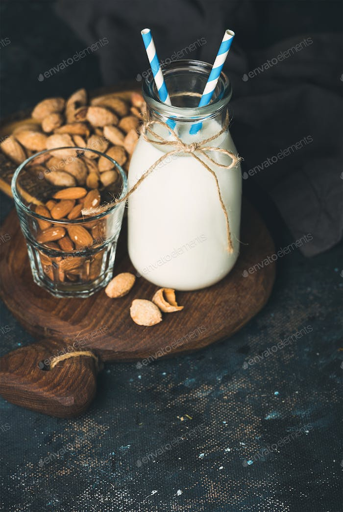 Fresh almond milk in glass bottle served with almonds