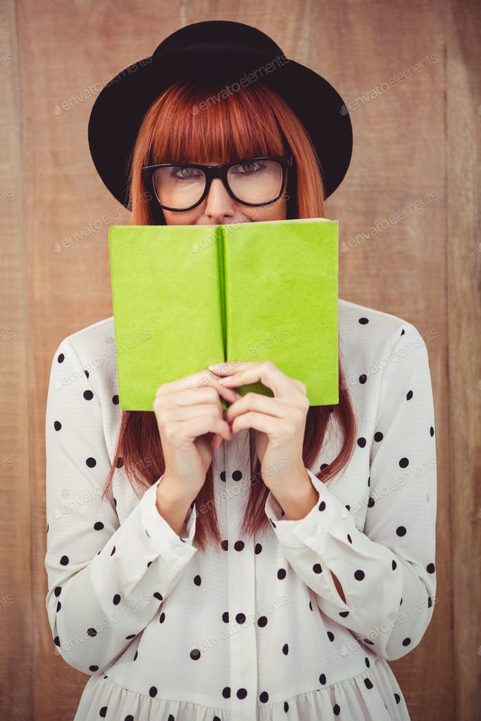 Hipster woman behind a green book against wooden background