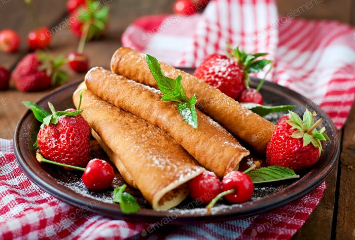 Pancakes with berries and syrup in a rustic style