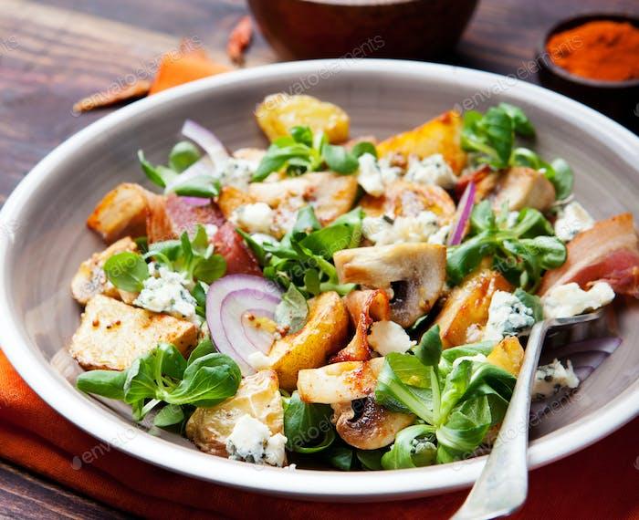 Potato salad with bacon, mushroom on orange napkin.