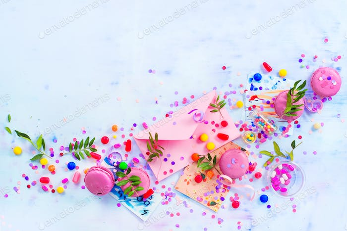 Love letter in a pink envelop with macarons, candies and confetti on a light background with copy
