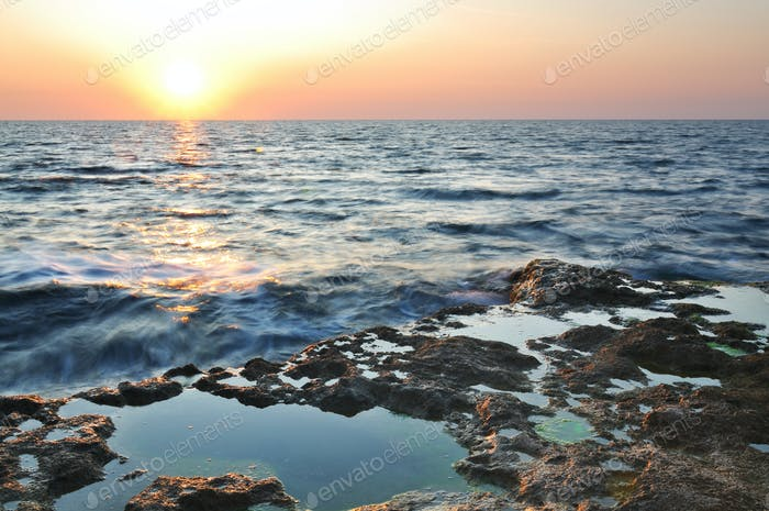 Beautiful pink sunset and water stones over Black sea rocky coastline in Crimea
