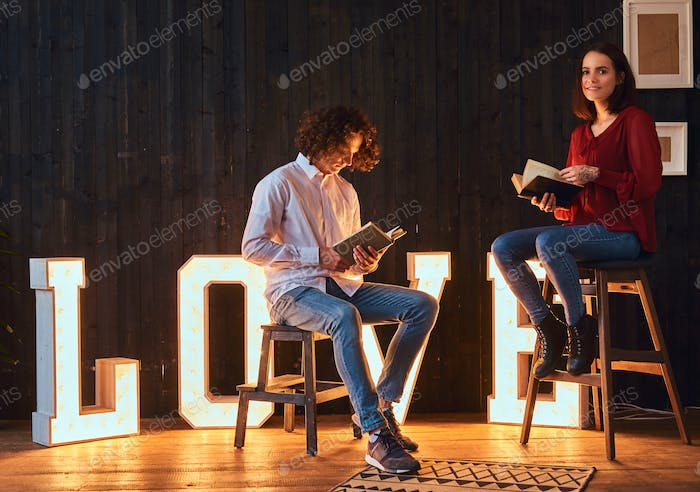 Young student couple reading together in a room decorated with voluminous letters with illumination.