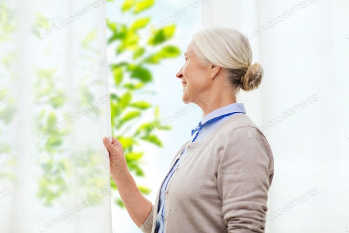 happy senior woman looking through window at home