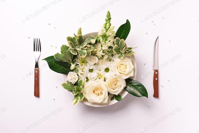 Weiße Blumen auf Teller, Gabel, Messer über hellem Hintergrund. Gesunde Ernährung, vegane Ernährung Konzept