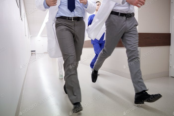 close up of medics or doctors running at hospital