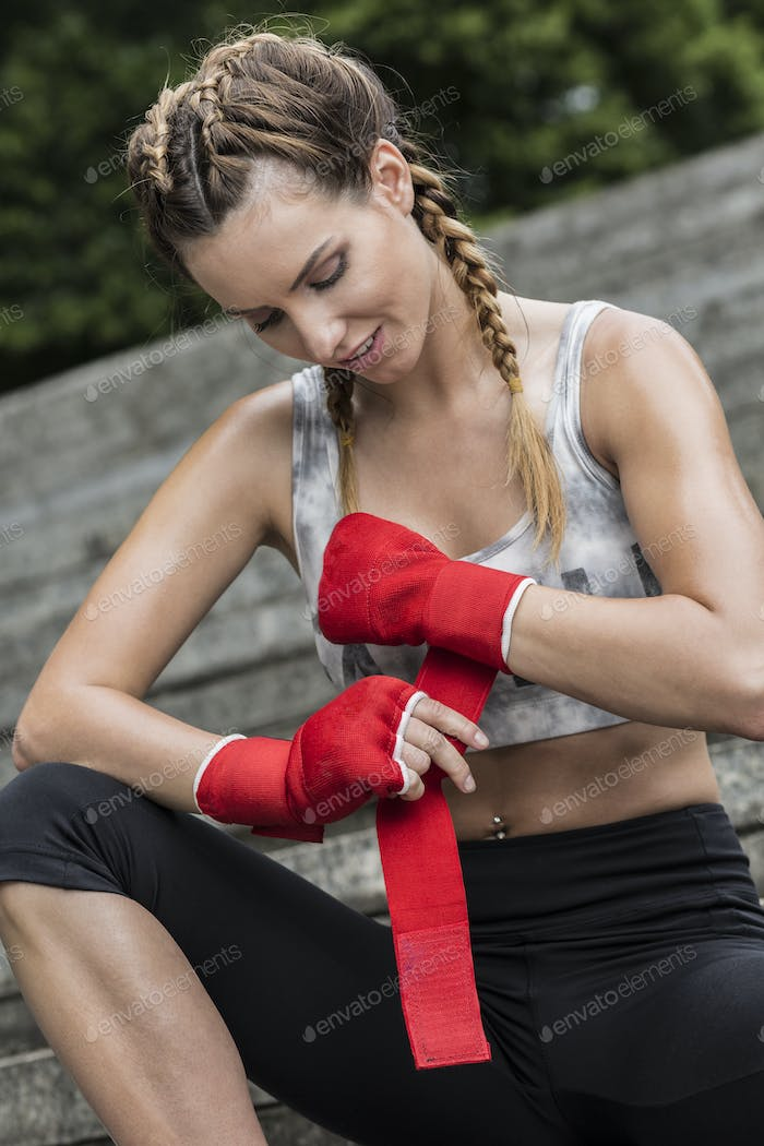 Fit woman wrapping her workout gloves