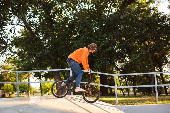Cool young guy in orange pullover and jeans riding bicycle and p