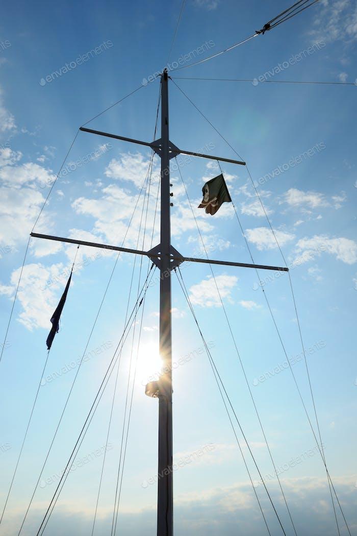 Mast on pleasure yacht on blue sky background
