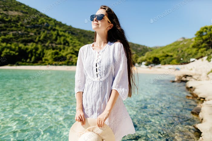 young woman relaxing on beach in summer dress