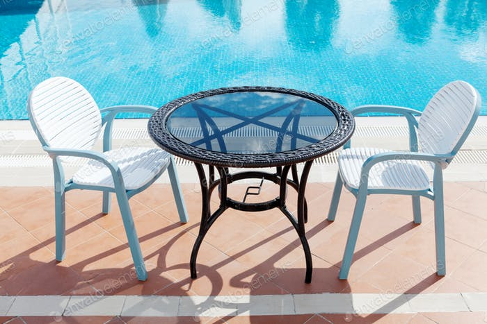 Sunny swimming pool, table and chairs
