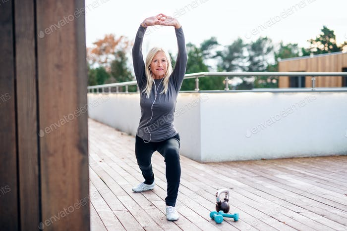 A senior woman doing exercise outdoors, stretching.