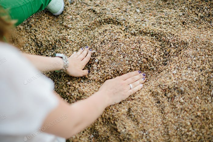 Woman drawing a heart in the sand