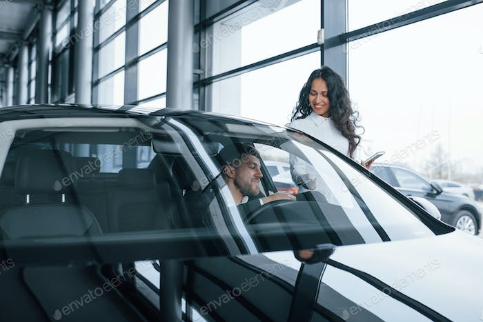Male customer and modern businesswoman in the automobile saloon