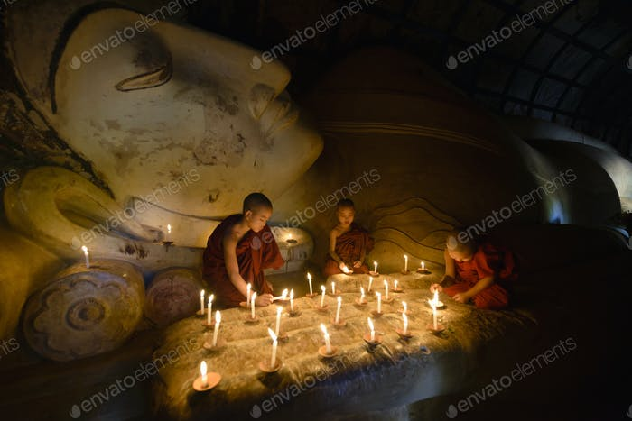 55059,Asian monks lighting candles in temple