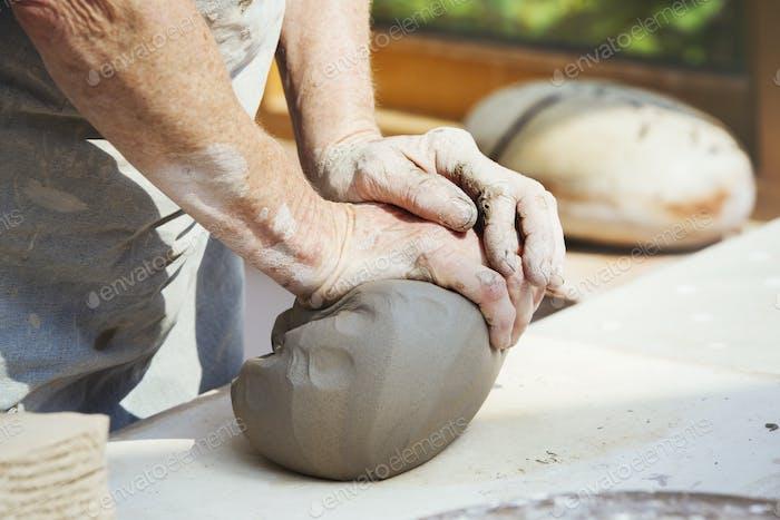 Una persona, alfarero preparando un trozo de arcilla húmeda para arrojar.