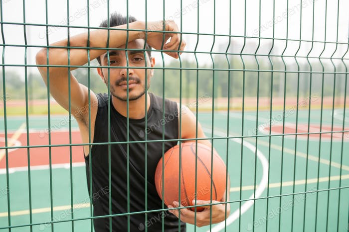 Serious male basketball player with ball standing against net