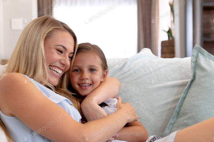 Caucasian woman and her daughter sitting on a couch and embracing at home