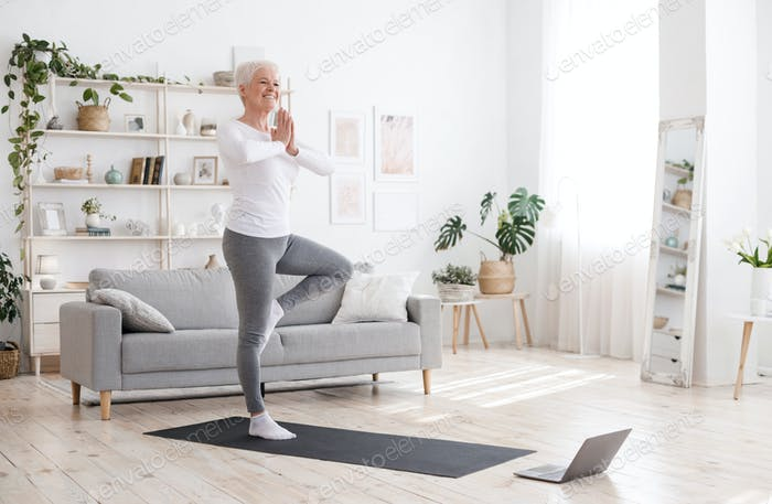 Sporty Senior Woman Practicing Yoga With Online Tutorials At Home