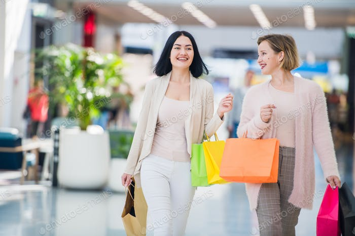 Sale, consumerism and people concept - happy young women with shopping bags walking and smiling in