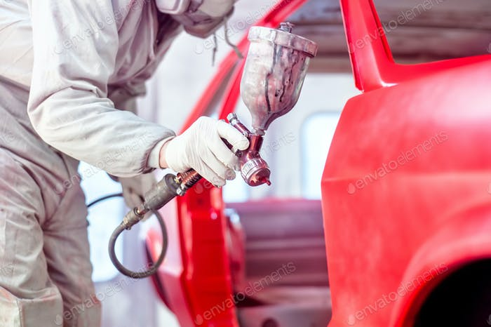 Professional worker spraying red paint on a car body