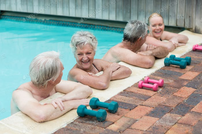 Cheerful swimmers leaning on poolside