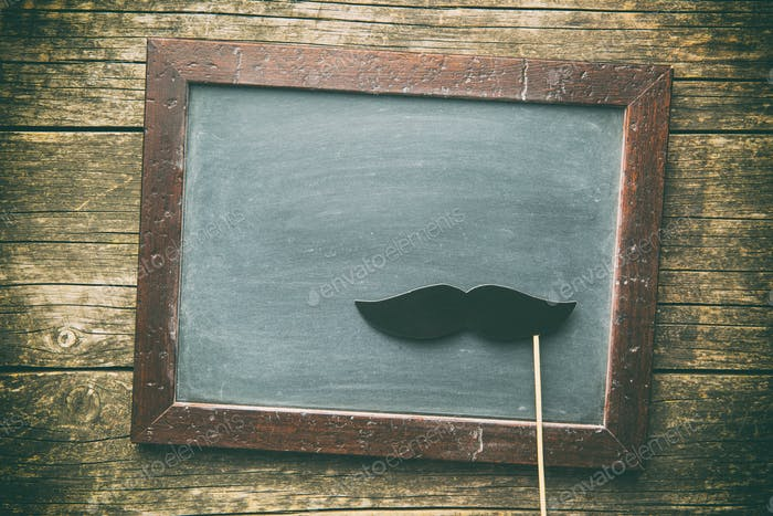 Blank chalkboard and fake mustache.