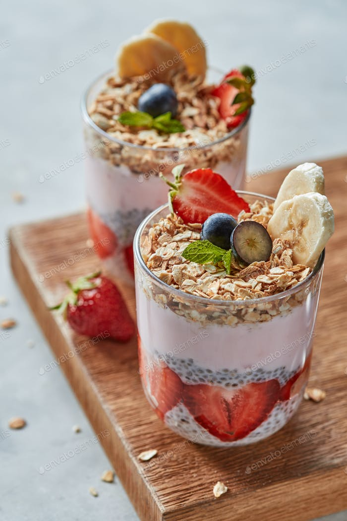 Natural organic ingredients for healthy breakfast in a glasses - oat granola, banana and strawberry