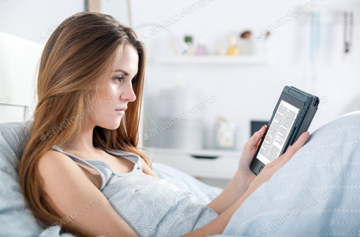Girl reading ebook on tablet reader in bed at home
