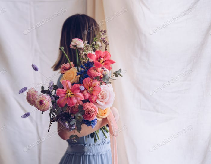 Young woman in a light blue dress holding a bouquet of flowers.