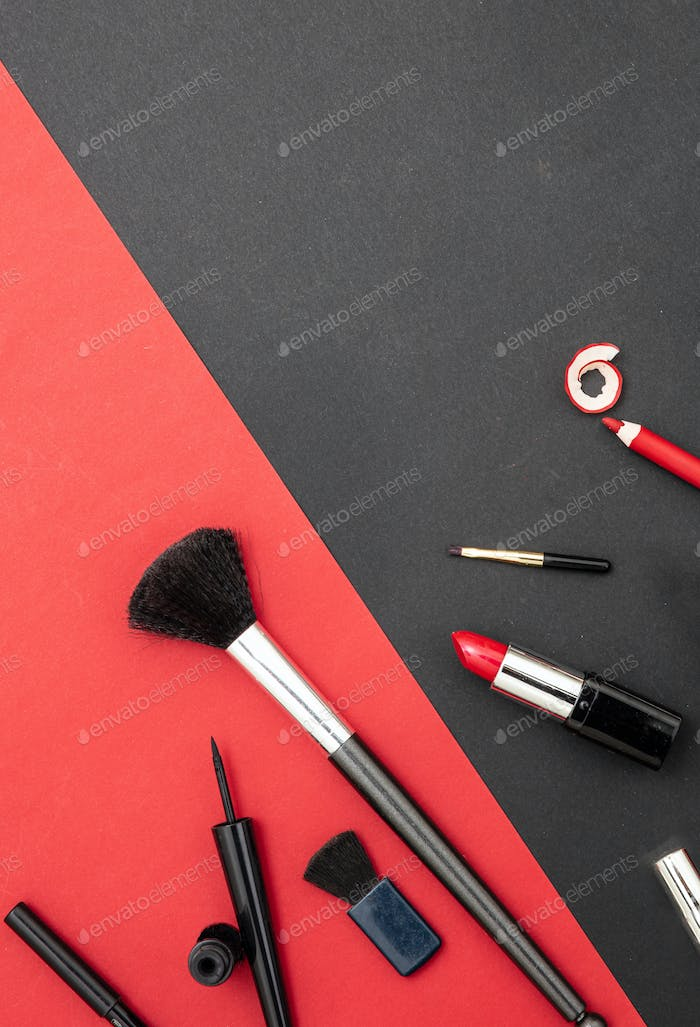 Make-up cosmetics accessories against red and black background