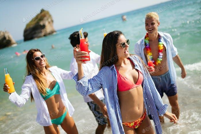 Grupo de Amigos Alegre de vacaciones divirtiéndose en la Playa en verano