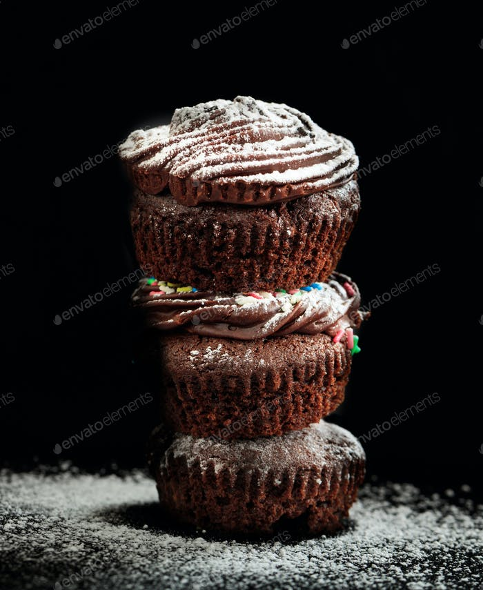 Chocolate cupcakes decorated with caster sugar on black background.