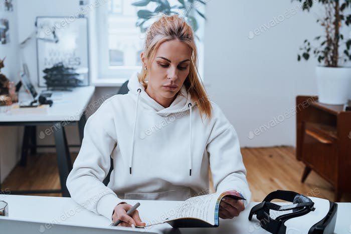 Concentrated woman works with laptop writing on notebook
