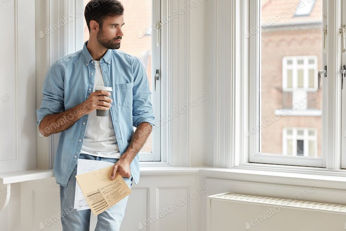 Horizontal shot of pensive unshaven guy recalls offer to start new business, studies documents, drin