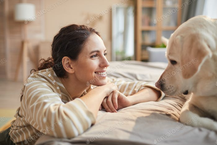 Happy Woman Talking to Dog at Home
