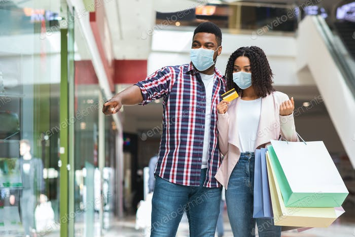 African American Couple In Medical Masks Shopping In Mall, Pointing At Showcase