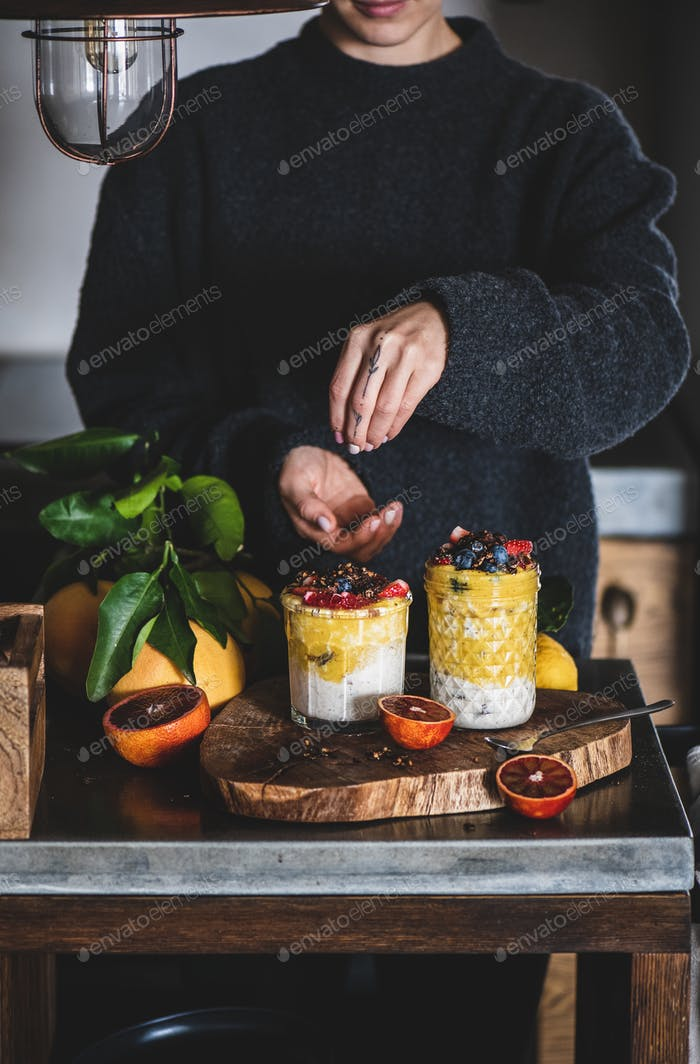 Woman putting ingredients to muesli with mango smoothie and granola
