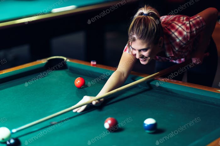 Young attractive woman playing pool in bar