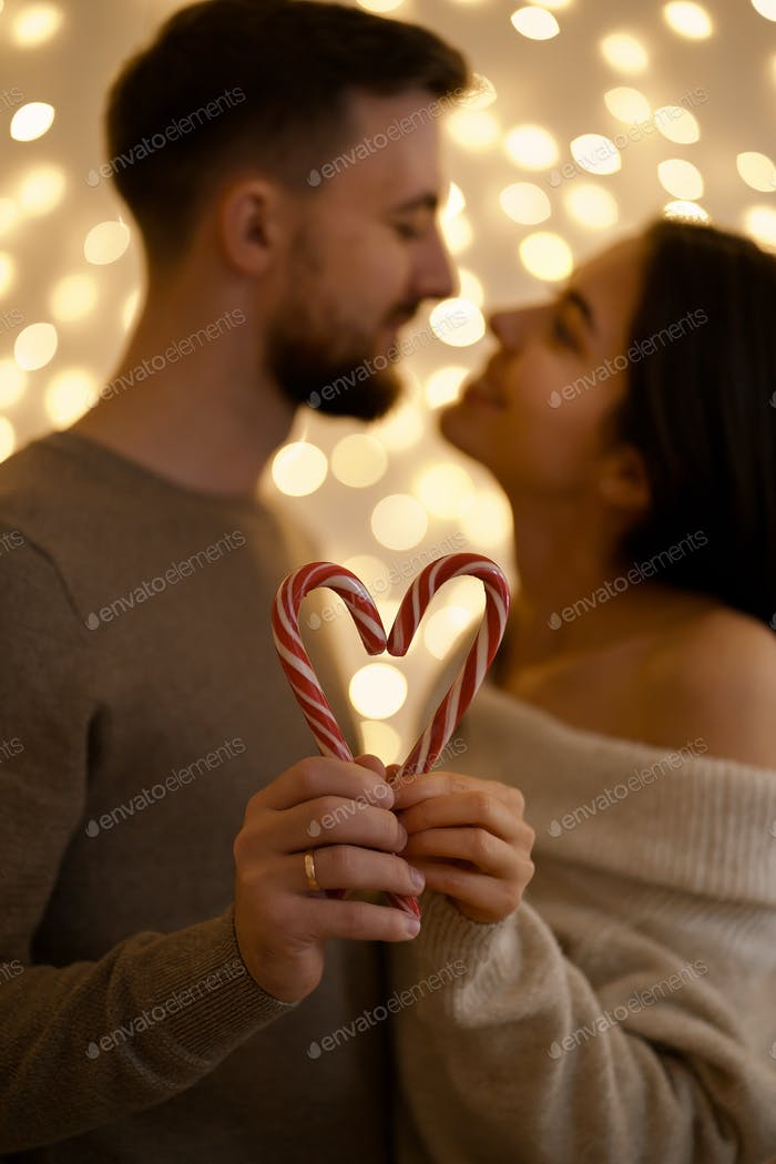 couple kissing and showing the heart-shaped figure of candy canes candies