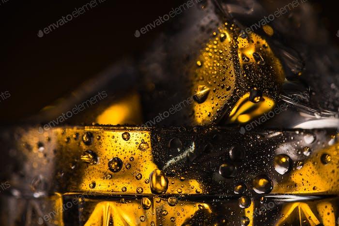 Nahaufnahme des quadratischen Eiswürfels in nassem facettiertem Glas mit gelber Beleuchtung