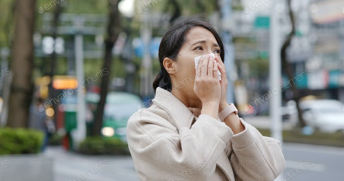 Woman sneeze in the city