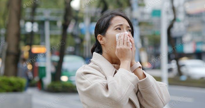 Frau niesen in der Stadt
