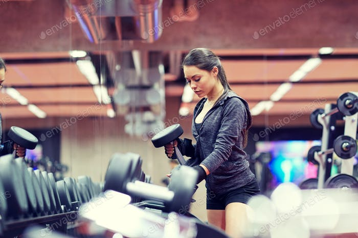 young woman choosing dumbbells in gym