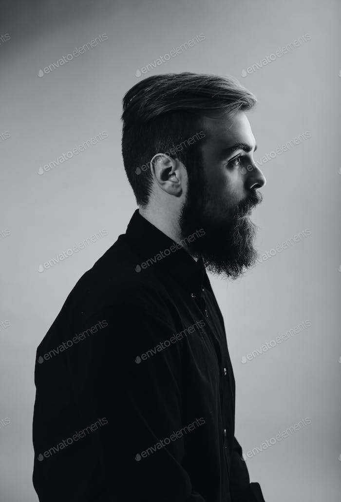 Black and white photo portrait of a man with a beard in profile dressed in the black shirt on the