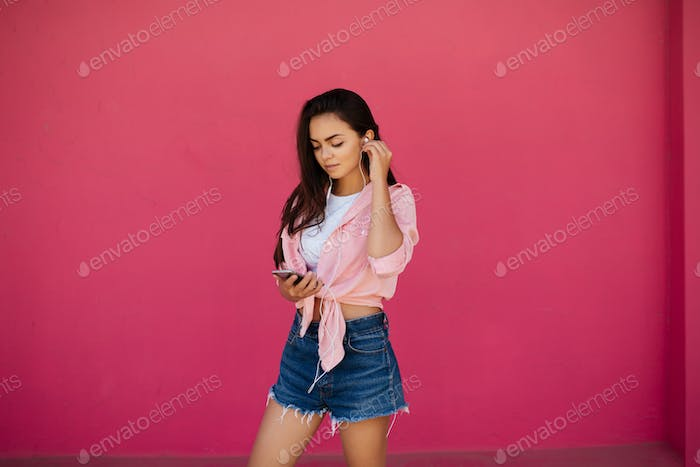 Young girl with dark hair using cellphone listening music in earphones on pink background