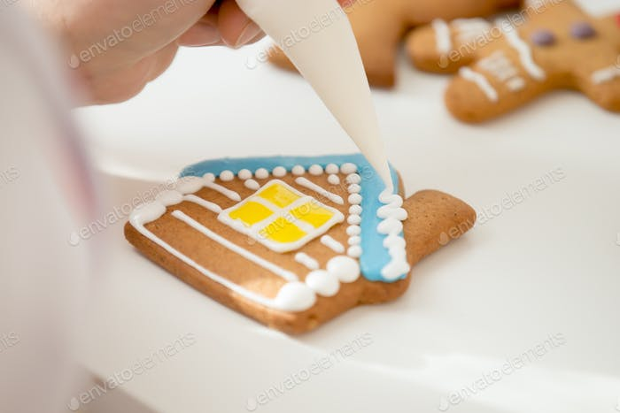 Close up of confectioner hand icing a gingerbread house
