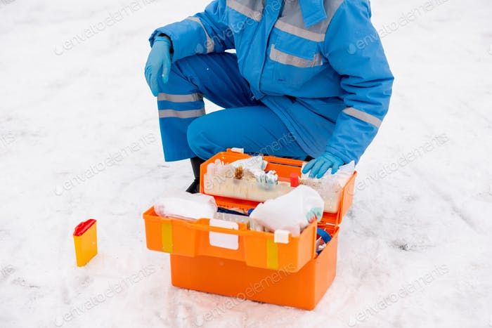 Young paramedic in workwear and gloves checking medicine and first aid items