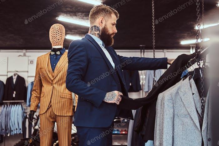 Элегантно одетый бородатый мужчина с татуировками на руках и шее выбирает новый костюм в магазине мужской одежды.